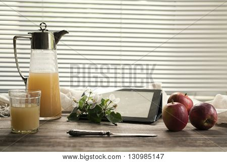 ancient jug of juice, apples and apple flowers on a glass table