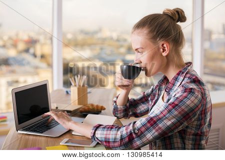 Drinking Coffee And Using Laptop