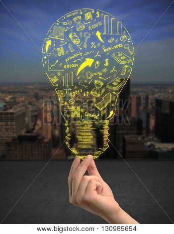 Idea concept with woman's hand holding abstract lightbulb sketch on night city background