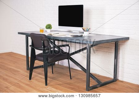 Sideview of designer desk with blank computer screen and brown chair next to it on wooden floor and brick background. Mock up