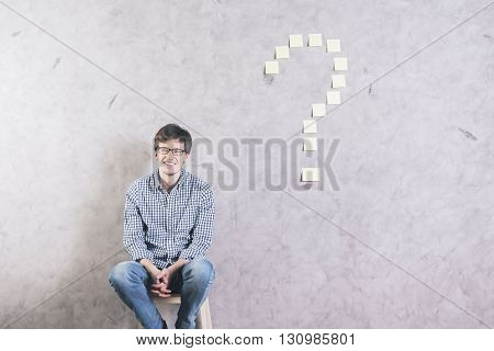 Smiling caucasian man sitting against concrete wall with sticker question mark