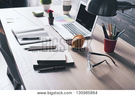 Closeup of backlit office desktop with laptop glasses orange slices on saucer plants coffee cup and various stationery items