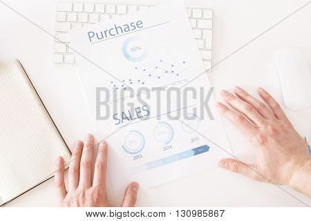 Topview of white workplace with male hands and business report
