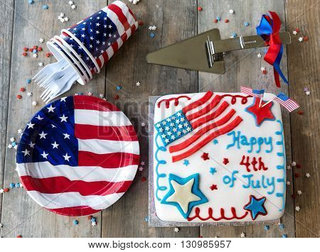 4th of July cake with plates and cups on wooden table, seen from above
