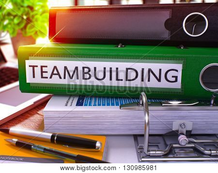 Green Ring Binder with Inscription Teambuilding on Background of Working Table with Office Supplies and Laptop. Teambuilding Business Concept on Blurred Background. 3D Render.