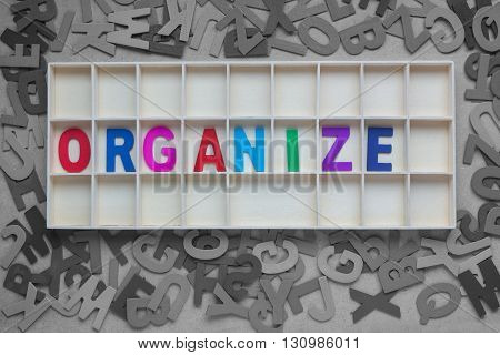 Wooden colored alphabets forming the word Organize in wooden box with scattered random wooden alphabets outside the box