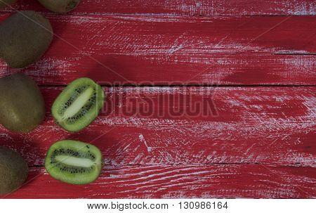 Old red wooden background with kiwi fruit