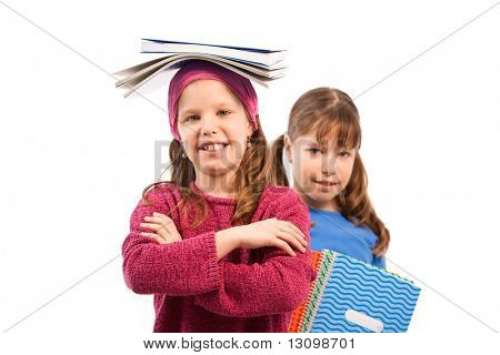 Portrait of shcoolchildren with workbooks, girls smiling at camera, balancing books on head.