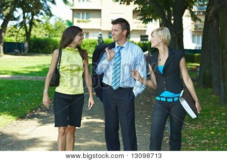 Young businesspeople walking and talking in downtown park.