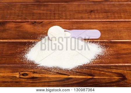 Mount wheat flour and spoon on dark wooden background.