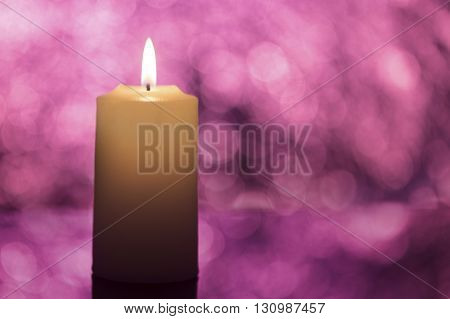 Candle shot in studio with violet bokeh lights in the background