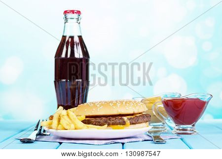 Fast food set hamburger, french fries, sauces and cola on a blue abstract background.