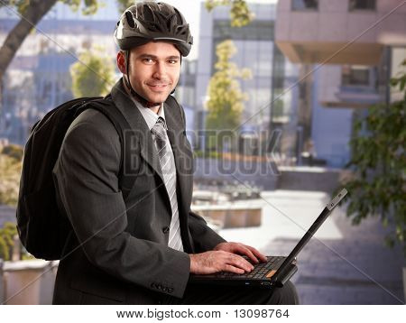 Portrait of young businessman wearing bike helmet, sitting in front of office building, using laptop computer.