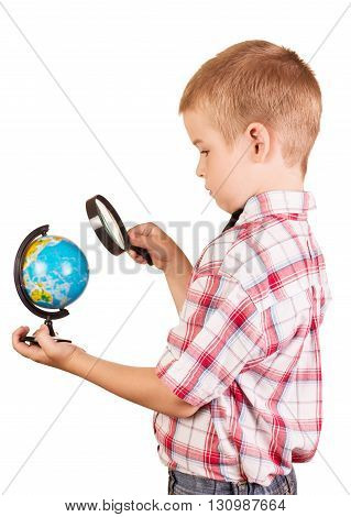 Schoolboy with a magnifying glass carefully examines the globe isolated on white background.