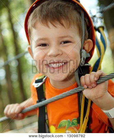 Retrato de niño feliz divirtiéndose en el Parque de aventura, sonriendo a la cámara que llevaba casco de montaña