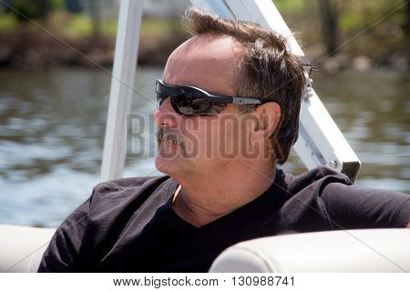 men portrait relaxing with sunglasses on a boat at summer