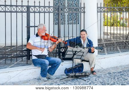 GREECE SANTORINI ISLAND - JULY 17/2014: Street musicians play music for people on the streets.