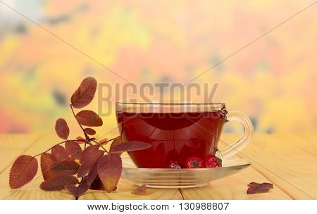 Cup of tea rosehip berries on a background of autumn leaves.