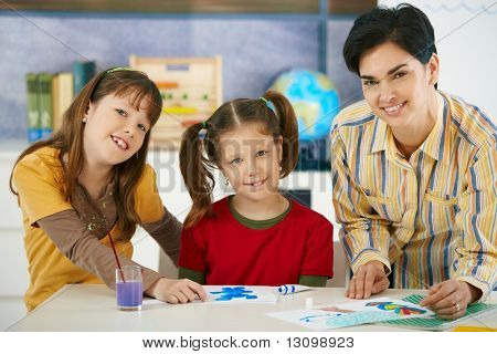 Portrait of elementary age children and teacher in art class in primary school classroom. Looking at camera, smiling.