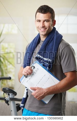 Handsome personal trainer with training plan.