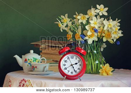 Retro still life with red alarm clock and a bouquet in the background.