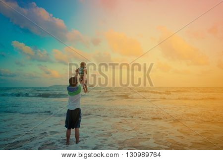 Father and son playing on the beach at sunset. Vintage tone
