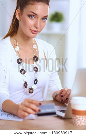 Businesswoman doing online shopping through laptop and credit card in office