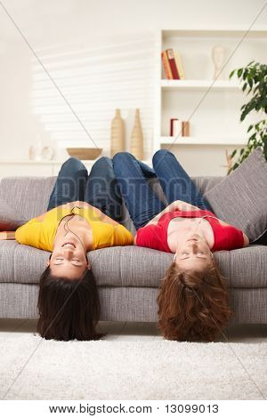 Teen girls lying on couch upside down, listening to music in earbuds, eyes closed.