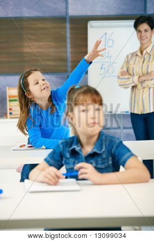 Schoolgirl in focus sitting in back row of class with raised hand, smiling, teacher standing at blackboard.