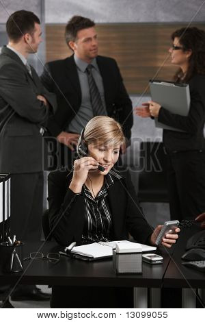 Young businesswoman sitting at desk in office, talking on headset, using PDA, smiling.