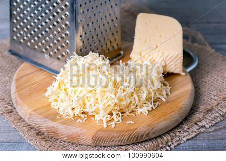 Grated cheese with grater on a wooden background
