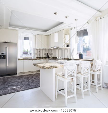 Spacious white kitchen with counter-top dining place