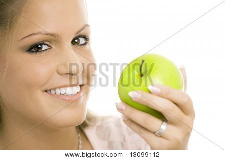 Closeup portrait of beautiful girl holding a green apple, smiling, isolated on white.