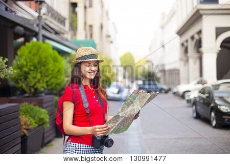 Portrait of a beautiful female tourist wearing hat searching a place on the map