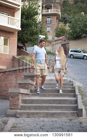 Happy couple in love walking in Tbilisi city Georgia. Young adults tourists on travel