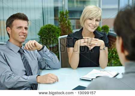 Happy business people sitting around table outdoor on office terrace and talking, smiling. Over the shoulder view.