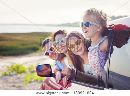 Portrait of a smiling family with two children at beach in the car. Holiday and travel concept