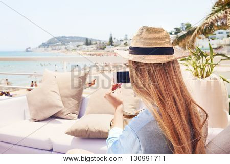 Happy young blond woman taking smartphone photo with smart phone of a beach in Gammarth Tunis Tunisia on outdoor patio sofa furniture
