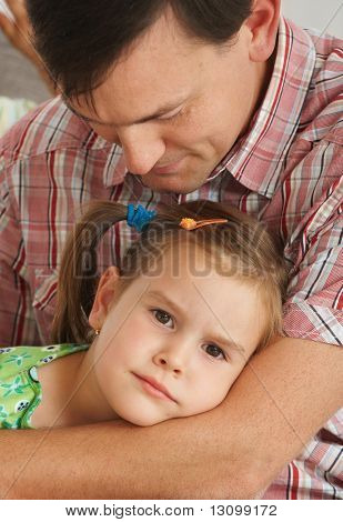 Portrait of little tired daughter resting with father, sitting.