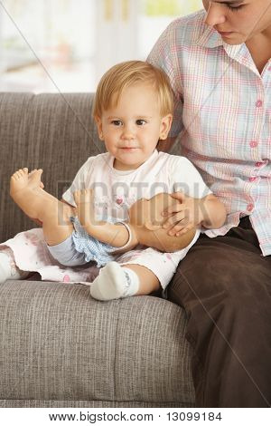 Cute toddler girl sitting on sofa with mother at home, smiling.