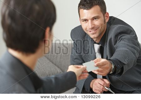 Business meeting at office lobby, people sitting on sofa changing business cards.