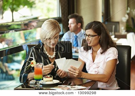Young women sitting in cafe having sweets, watching photos, smiling.