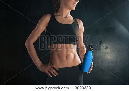 Muscular young woman athlete drinking water on black background.
