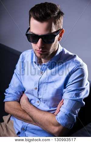 Unhappy Handsome Man In Sunglasses Sitting On Sofa And Thinking About Something