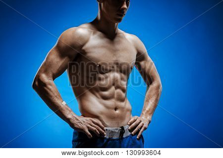The fit young man with beautiful torso on blue background