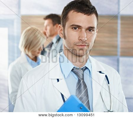 Healthcare workers on hospital corridor mid-adult doctor in front looking at camera, smiling.