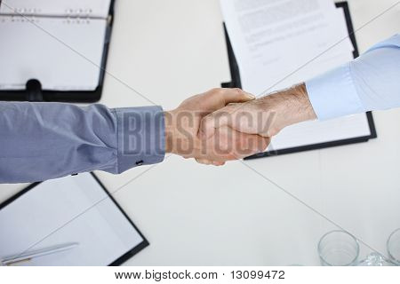 Closeup of hands, businessmen shaking hand over meeting table in office.