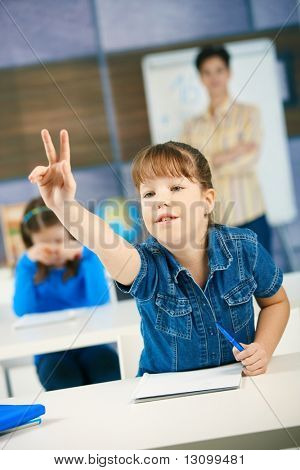 Schoolgirl raising hand to answer question smiling, other girl and teacher in background of class.