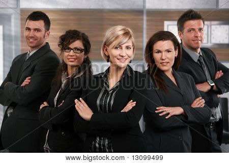 Team of successful happy businesspeople standing in office, businesswoman in front smiling.