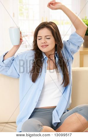 Pretty girl stretching on couch with arms raised, holding coffee cup, smiling with closed eyes.